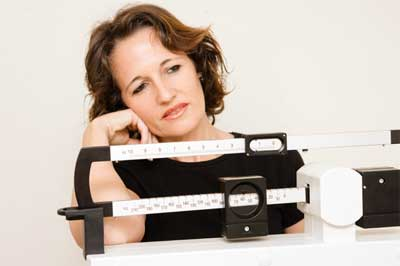 Woman weighting herself on scale - weight loss plateau