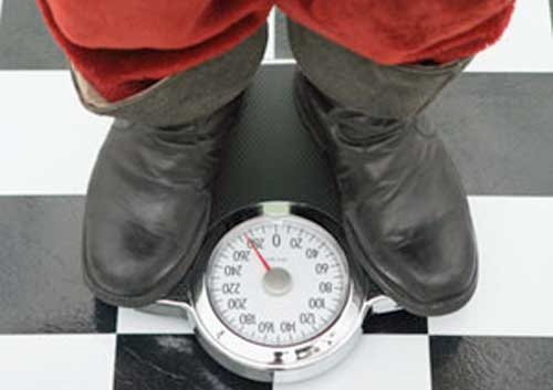 santa clause on scale How to Prevent Holiday Weight Gain?