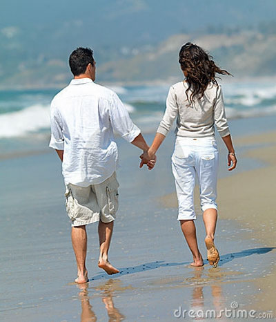 man and woman holding hands walking on beach sober