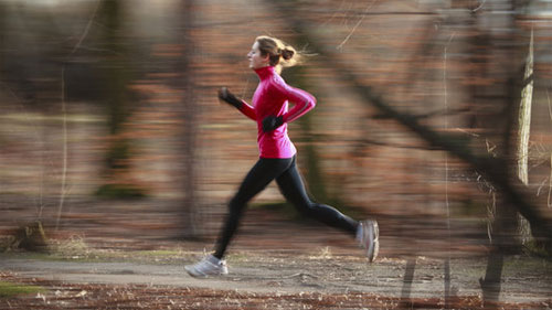 woman running in the woods in the fall